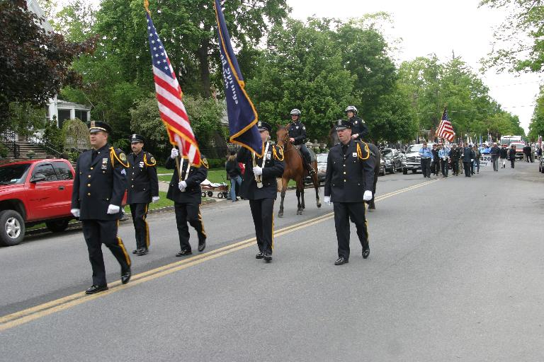 Officers walk down street during parade
